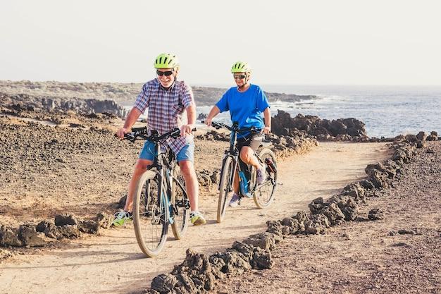 Para dwóch seniorów jeżdżących razem na rowerach na ziemi, dobrze się bawiąc - wykonując ćwiczenia, aby być zdrowym i sprawnym