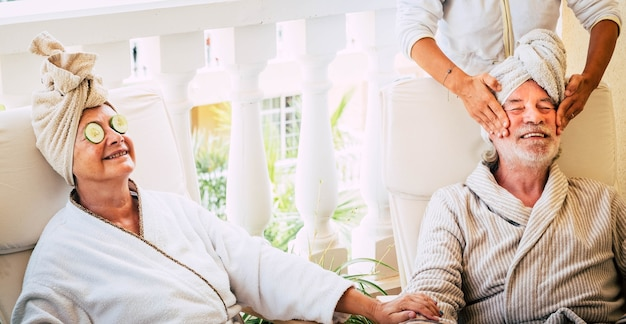 Para dwóch seniorów robi zabieg kosmetyczny wraz z asystą podczas masażu u jednego emeryta, podczas gdy jego żona uśmiecha się z cukinią w oczach - aktywny i zdrowy tryb życia
