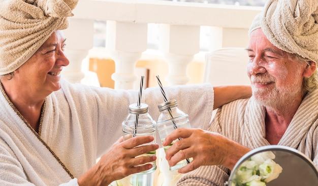 Para dwóch seniorów w kurorcie lub hotelu pijąca koktajl i stukająca się - emeryci zrelaksowani zabiegiem kosmetycznym