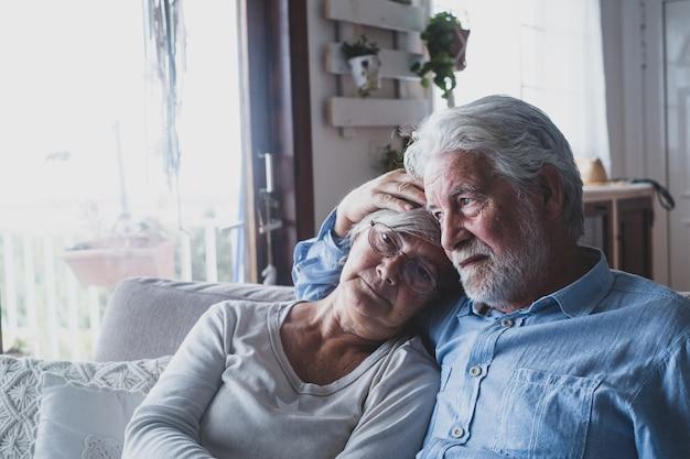 Para dwóch smutnych i przygnębionych starych ludzi siedzących na kanapie w domu patrząc przez okno. zamknięcie i kwarantanna wewnątrz pomieszczeń.