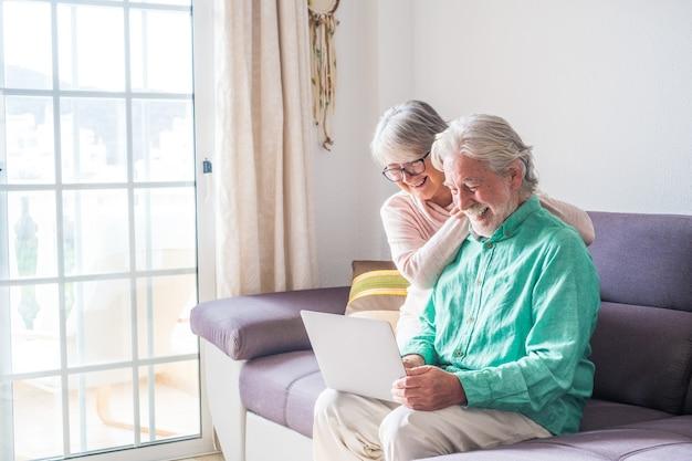 Para dwóch starych i dojrzałych ludzi w domu za pomocą tabletu razem w kanapie. senior używać laptopa, bawiąc się i ciesząc się, patrząc na niego. koncepcja czasu wolnego i wolnego