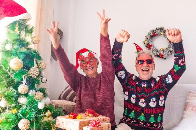 Para dwóch szalonych i zabawnych seniorów bawiących się razem i świętujących przyjęcie w domu w boże narodzenie przed zapakowaniem prezentów i prezentów