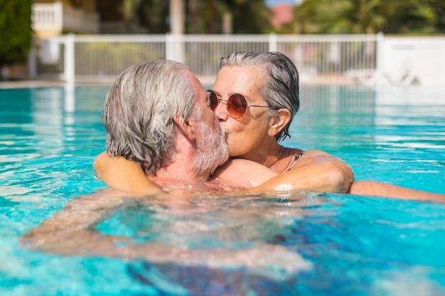 Para dwóch szczęśliwych seniorów zabawy i wspólnej zabawy w basenie, uśmiechając się i grając. szczęśliwi ludzie cieszący się latem na świeżym powietrzu w wodzie