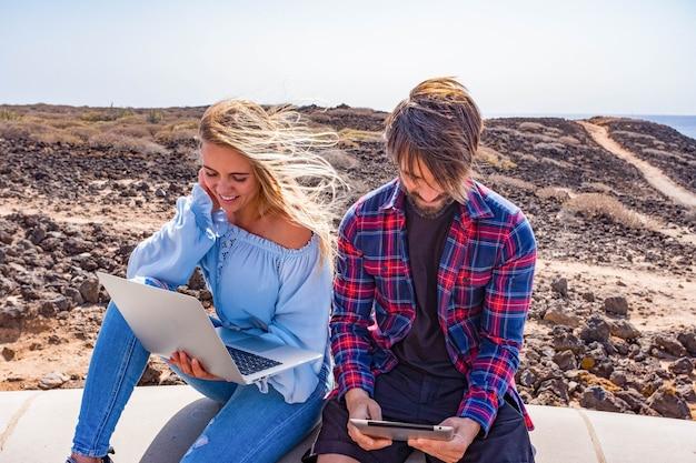 Para dwojga dorosłych korzystających z laptopa i ipada razem na zewnątrz - koncepcja technologii i styl życia online - piękna kobieta i przystojny mężczyzna bawią się razem