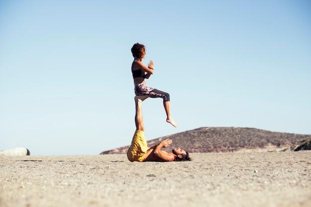Para dwojga dorosłych w związku lub przyjaźni uprawiających razem acro jogę - mężczyzna trzymający nogami kobietę, gdy ona siedzi
