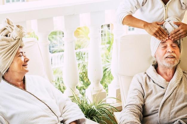Para dwojga emerytów w resorcie robi zabieg kosmetyczny wraz z kobietą asystującą podczas masażu u mężczyzny - dojrzali ludzie w hotelu zrelaksowani