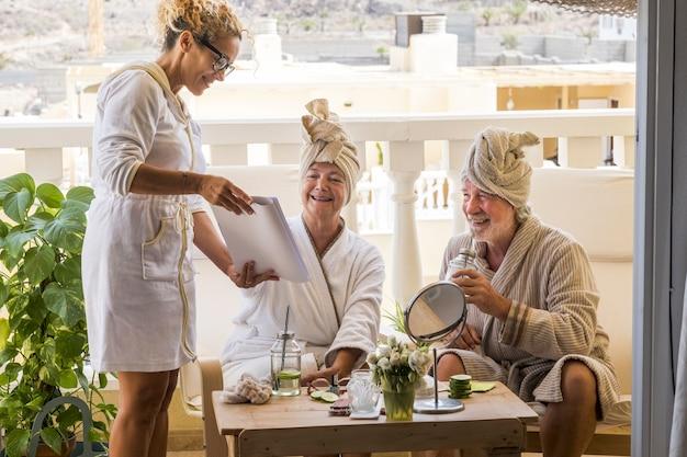 Para dwojga emerytów w resorcie robi zabieg kosmetyczny wraz z panią asystującą pokazującą menu - dojrzali ludzie w domu zrelaksowani