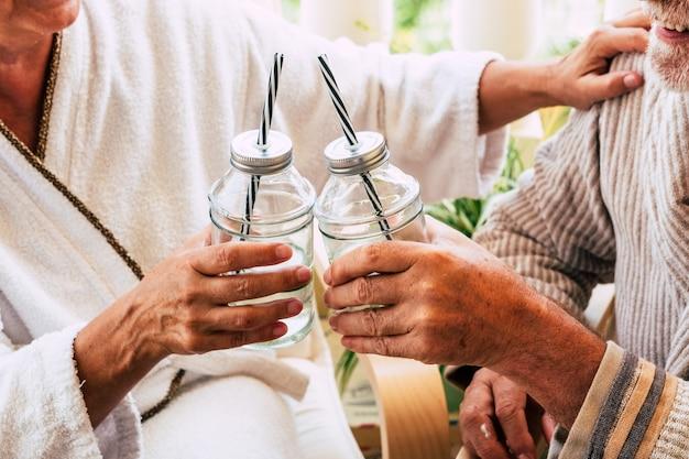Para dwojga seniorów lub dojrzałych osób biorących razem drinka lub koktajl w domu lub w hotelu podczas masażu
