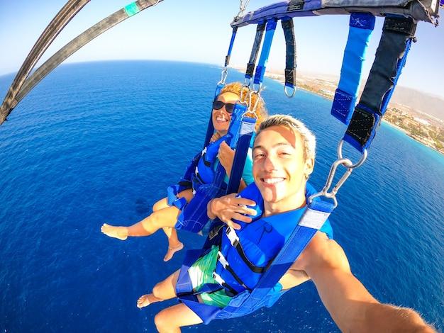 Para dwojga szczęśliwych ludzi cieszących się latem i wakacjami, wykonujących ekstremalną aktywność na morzu z łodzią - piękni ludzie biorący selfie podczas wspólnego wznoszenia się na spadochronie
