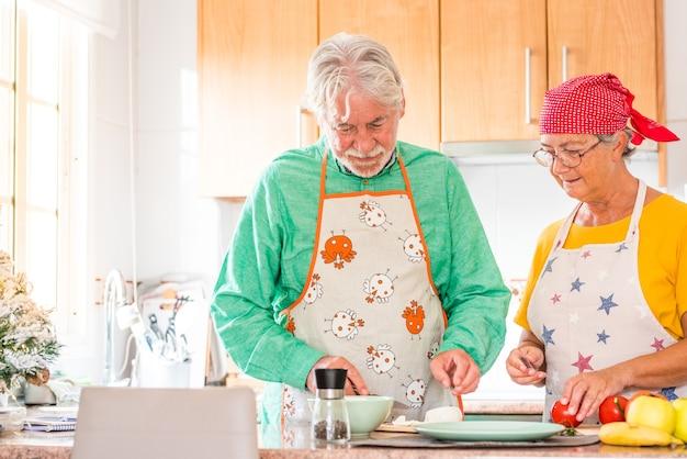 Para Dwojga Szczęśliwych Seniorów Bawi Się I Gotuje Razem W Domowej Kuchni - Przygotowując Zdrowe Jedzenie Z Pomidorami Premium Zdjęcia