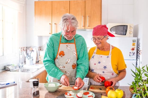 Para dwojga szczęśliwych seniorów bawi się i gotuje razem w domowej kuchni - przygotowując zdrowe jedzenie z pomidorami