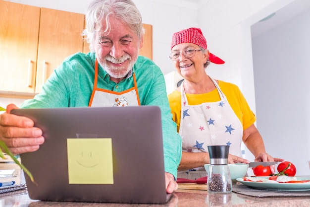 Para dwojga szczęśliwych seniorów gotujących razem w kuchni, ucząca się i podążająca za samouczkiem wideo kucharza w laptopie - wspólne przygotowywanie zdrowego jedzenia