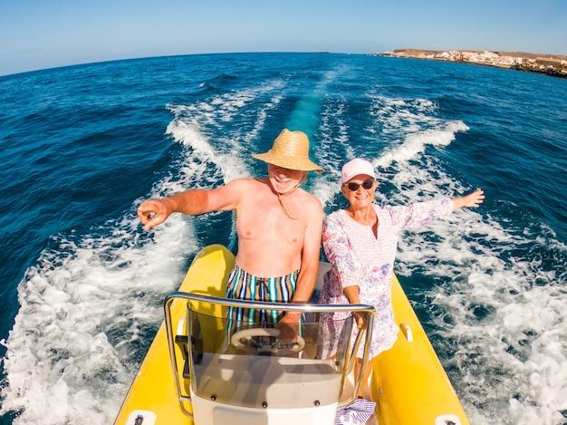 Para dwojga szczęśliwych seniorów i dojrzałych ludzi korzystających i prowadzących małą łódkę lub ponton