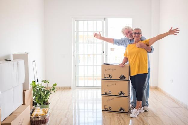 Para dwojga uśmiechniętych starszych ludzi szczęśliwych w nowym pustym domu na nowy początek, jak na emeryturze z przesuwającymi się pudłami na podłodze