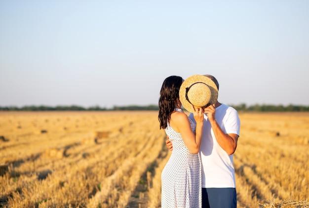 Para dwojga zakochanych stoi na boisku, całując się za słomkowym kapeluszem