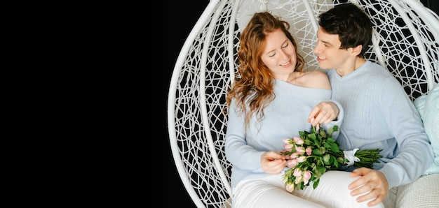 Para dziewczyna i facet przytulanie na dużym krześle z bukietem róż. biało-niebieski sweter.