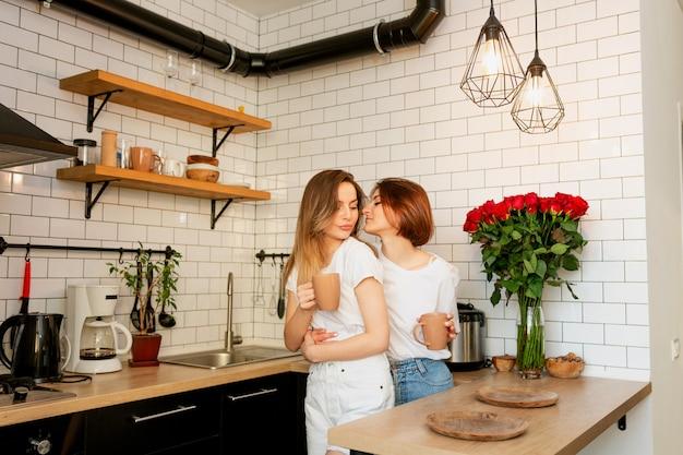 Para dziewczyna przytulanie w kuchni w walentynki i picie kawy