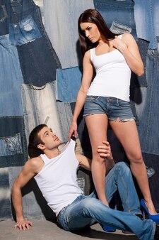 Para dżinsów. piękna młoda para w podkoszulkach i dżinsach stojących pozowanie na tle dżinsów