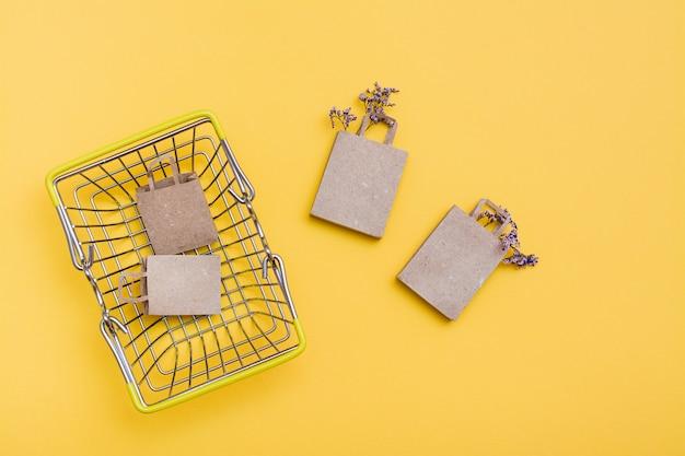 Para ekologicznych papierowych torebek rzemieślniczych w metalowym koszu na zakupy z suszonymi kwiatami na żółtym tle i w jego pobliżu. wyprzedaż prezentów w czarny piątek