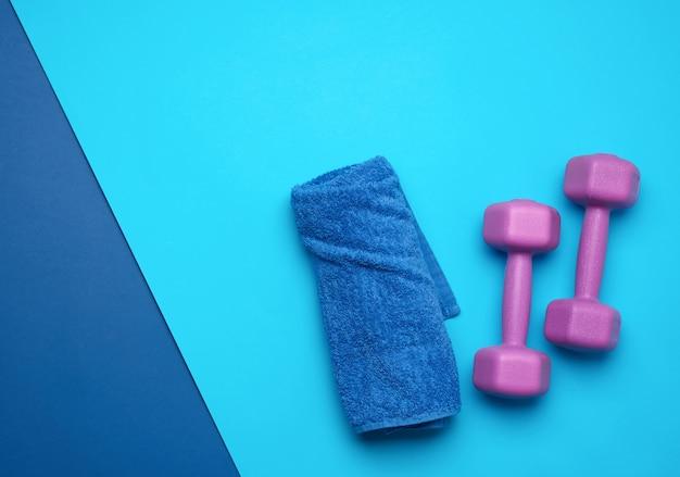 Para fioletowych hantli i niebieski ręcznik na niebieskim tle