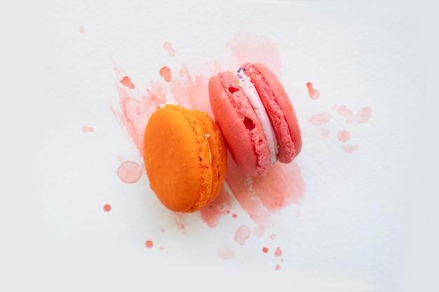 Para francuskich ciasteczek makaroników na tle akwareli, widok z góry