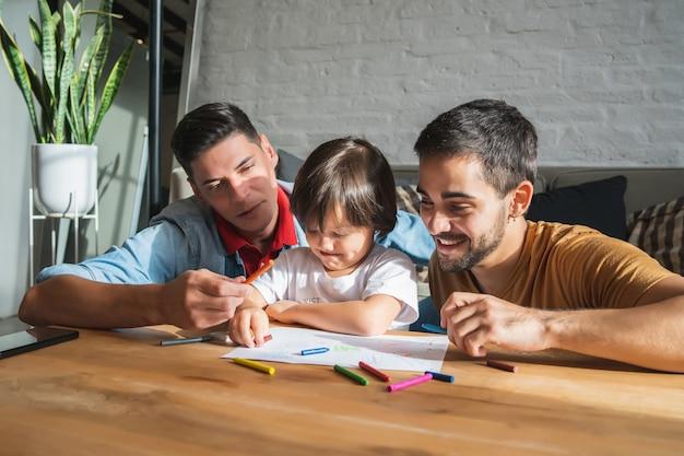 Para gejów i ich syn bawią się razem podczas rysowania czegoś na papierze w domu. koncepcja rodziny.