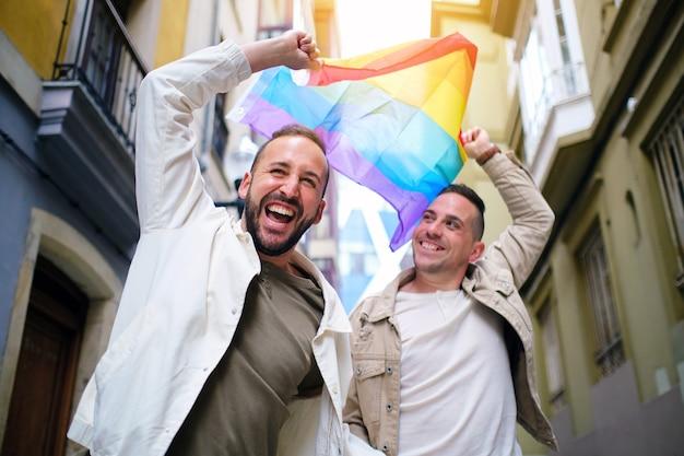Para gejów świętuje tęczową flagą w dzień dumy