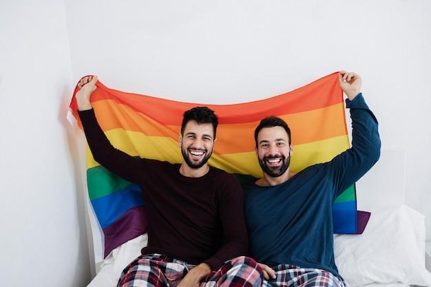 Para gejów trzymająca tęczową flagę lgbt w pomieszczeniu na łóżku w domu - główny nacisk na lewą twarz mężczyzny