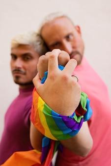 Para gejów z flagą lgbt trzymając się za ręce