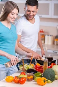 Para gotowania obiadu. szczęśliwa młoda para gotuje obiad w kuchni