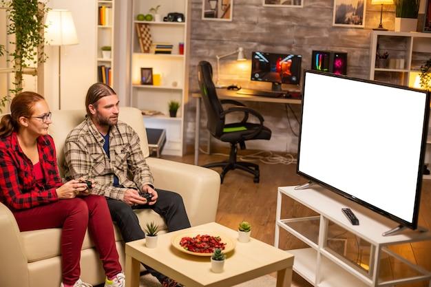 Para grająca w gry wideo na izolowanym białym ekranie telewizora późno w nocy w salonie