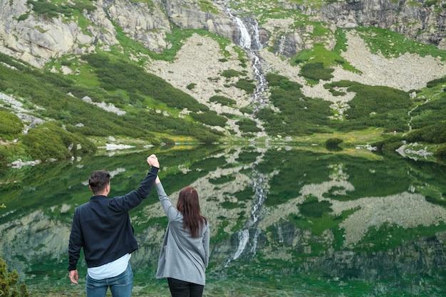 Para heteroseksualna trzymając się za ręce przed niesamowitym widokiem na wodospad