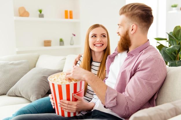 Para jedzenie popcornu na kanapie w domu i oglądanie telewizji