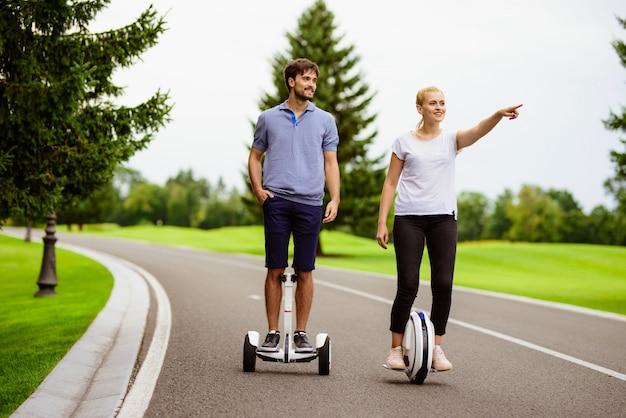 Para jedzie na gyroboardzie i monoklu w parku.