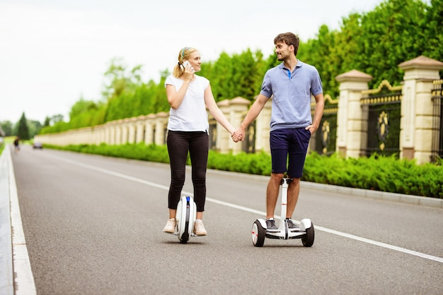 Para jedzie na gyroboardzie i monoklu w wiejskim parku.
