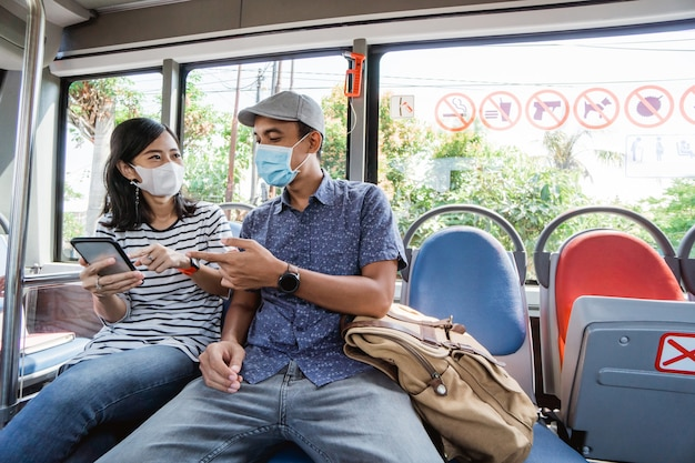 Para jedzie razem w publicznym autobusie w masce na twarz