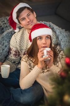 Para jest ubranym santa kapelusze z gorącymi napojami