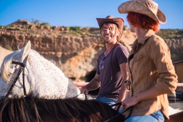 Para jeźdźców i koni razem na drodze w górach. odkrywaj i podróżuj po świecie w alternatywny sposób. ciesz się naturą i poczuj ciszę. zachodnia scena koncepcyjna