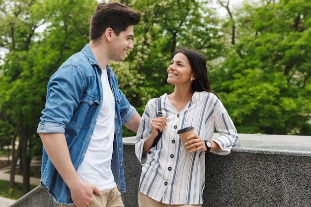 Para kaukaska mężczyzna i kobieta z papierowym kubkiem uśmiechający się i rozmawiający stojąc na schodach na zewnątrz
