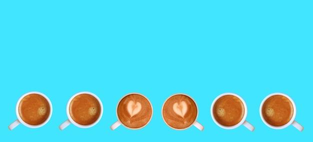 Para kawy cappuccino latte art w kształcie serca z kawą espresso w linii na niebieskim tle