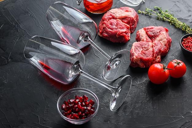 Para kieliszek do czerwonego wina w pobliżu kawałków surowej wołowiny ekologicznej, z rozmarynem, pikantnym olejem chili na czarnym tle z teksturą widok z boku.