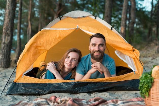 Para kłaść w namiocie patrzeje kamerę