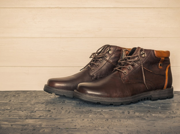 Para klasycznych brązowych butów męskich na drewnianych ścianach z ciemną podłogą. brutalne buty męskie.