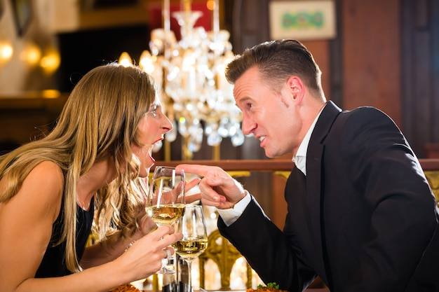 Para kłóci się o romantyczną restaurację na randce. są źli i krzyczą, duży żyrandol