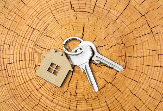 Para kluczy do domu z brelokiem w kształcie domu na ściętym pniu drzewa na tle słojów wzrostu. widok z góry. skopiuj miejsce