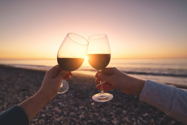 Para kochanków pije czerwone wino podczas oglądania zachodu słońca i ciesząc się wakacje na morzu w miesiącu miodowym
