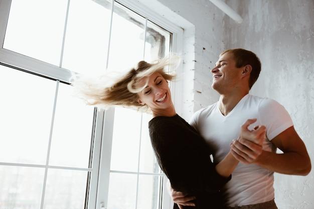 Para kochanków, przytul, pocałuj, śmiej się. dziewczyna w długim czarnym swetrze i białym golfie. jasnoszare wnętrze, duże okno, brązowe stylowe krzesło.