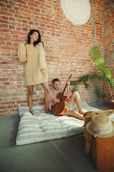 Para kochanków razem relaks w domu. kaukaski mężczyzna gra na gitarze podczas tańca kobiety. mając weekend, wygląda czule i szczęśliwie. pojęcie relacji, komfortu rodzinnego, jesienno-zimowego.