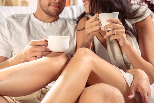 Para kochanków razem relaks w domu. kaukaski mężczyzna i kobieta weekend, wygląda czule i szczęśliwie
