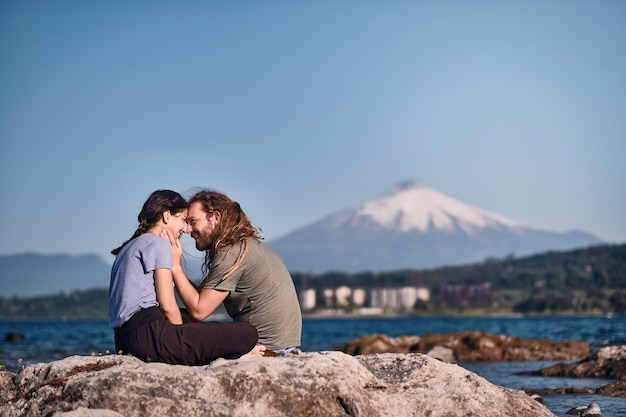 Para kochanków siedzi na skale, patrzy na siebie i pieści z uśmiechem